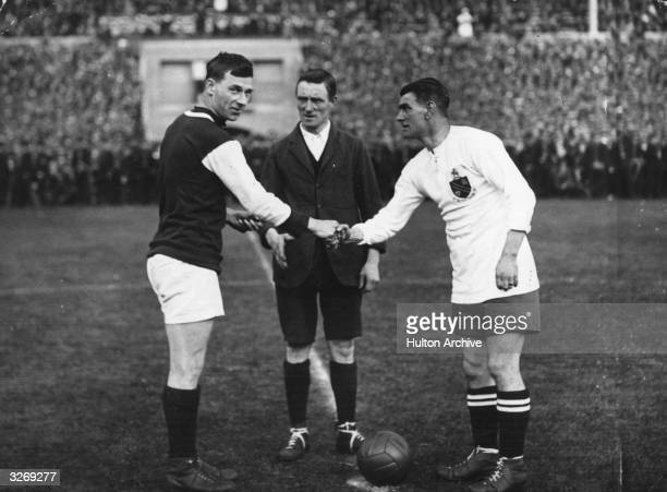 Watched by the referee G Kay captain of West Ham United and Joe Smith captain of Bolton Wanderers shake hands before the kick off of the first ever...
