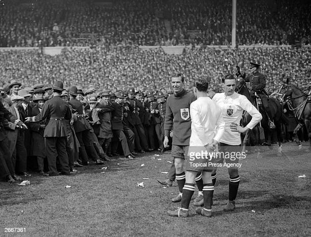 West Ham United and Bolton Wanderers players wait for the police to clear the pitch of spectators and allow the FA Cup final to kick off after a 45...