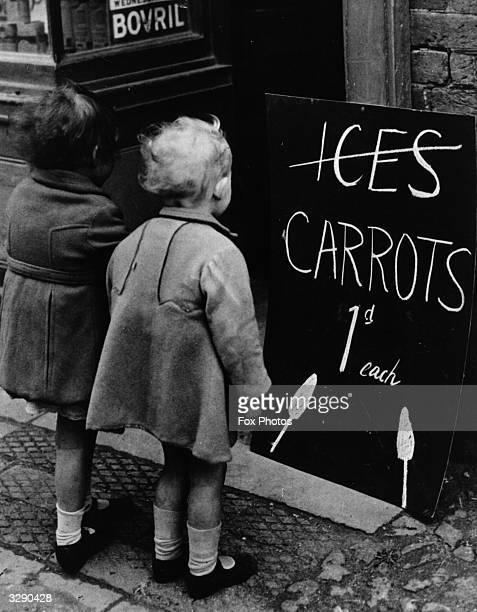 Two little girls reading a board advertising carrots instead of ice lollies Wartime shortages of chocolate and ice cream made such substitutions a...