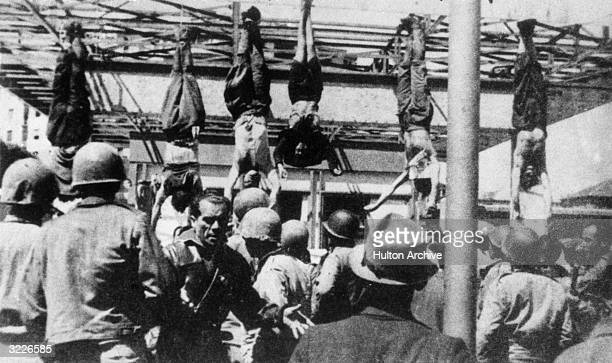 Italian fascist leader Benito Mussolini and others captured with him, including his mistress, Clara Petacci, hang by their feet from a filling...