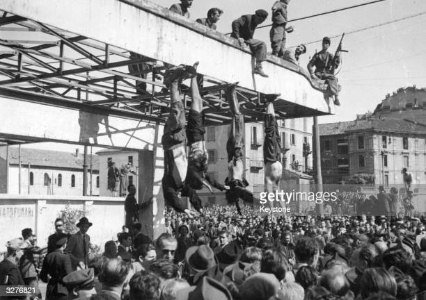 The bodies of Benito Mussolini and Clara Petacci, his mistress, hang from the roof of a gasoline station after they had been shot by anti-Fascist...