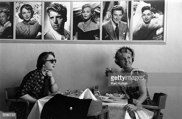 Film fans eating under pictures of the Hollywood greats in Los Angeles California Original Publication Picture Post 5298 We Go To Hollywood pub 1951