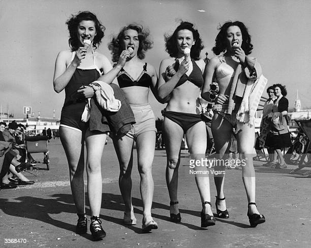 Four revue dancers strolling along the front at Southend on Sea in Essex dressed for the hot weather and ejoying an ice cream