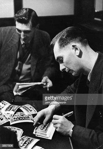 Jackie Milburn of Newcastle United signing his autograph on team photographs. Original Publication: Picture Post - 5295 - Twenty-Two Very Ordinary...