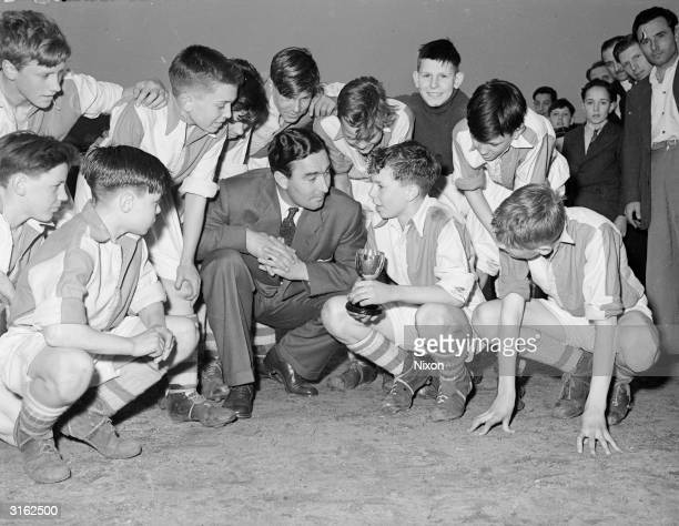 British cricketer and footballer Denis Compton with the Acton Brentford and Chiswick schoolboys who won the Compton trophy