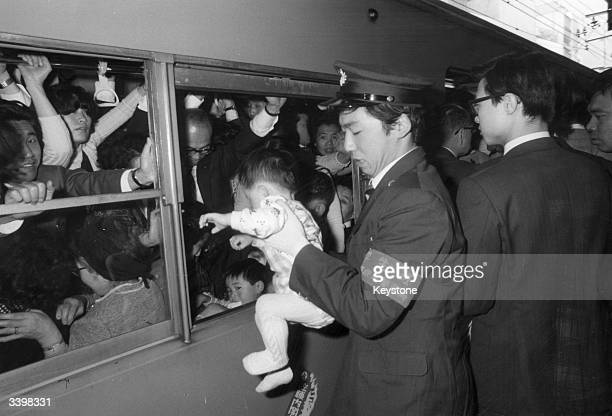 A platform attendant passes a baby into the window of a crowded train in Tokyo during a strike by Japanese railway workers