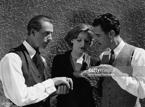 From left to right Lars Hanson Greta Garbo and John Gilbert examine each others' rings on the set of 'Flesh and the Devil' directed by Clarence Brown