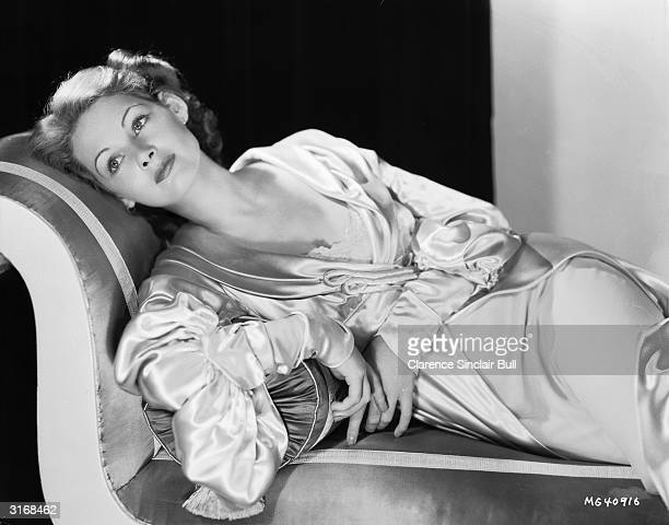 English stage and screen actress Elizabeth Allan wearing a luxurious satin robe reclines on a chaise longue