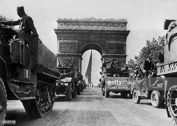 Armoured vehicles of the Free French leading a victory parade under the Arc de Triomphe in one of the greatest celebrations ever held in the French...