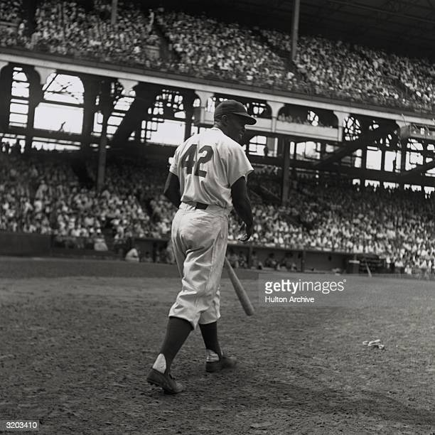 American baseball player Jackie Robinson, second baseman for the Brooklyn Dodgers, steps up to bat with his back to the camera during a game at a...
