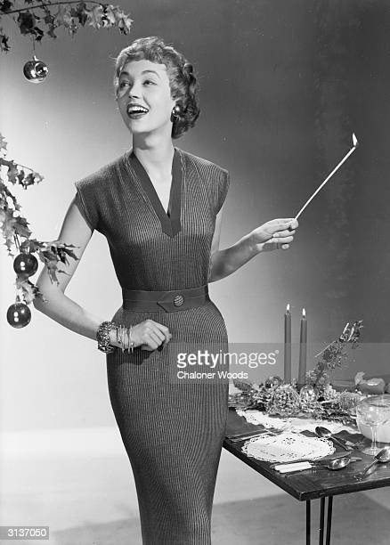 A woman in a fitted dress with a Vneck lights the candles at a table laid for Christmas dinner
