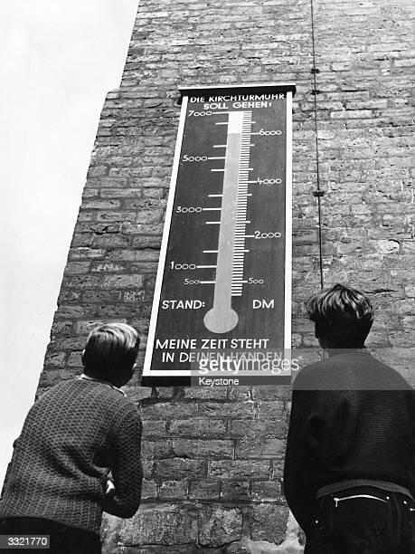 Two boys looking up at the 600yearold Nikolai Church's 'Save The Church Steeple Appeal' in Spandau East Berlin