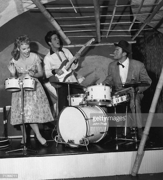 Sylvia Syms plays bongos with Cliff Richard on guitar and Laurence Harvey on drums during the making of 'Expresso Bongo' directed by Val Guest and...
