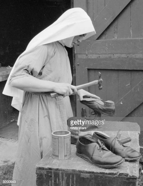 A nun learns to mend shoes at Ladywell Convent Godalming Surrey All the Sisters acquire practical skills at the convent to prepare them for...