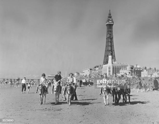 Holidaymakers riding donkeys on a busy beach in Blackpool, Lancashire with Blackpool Tower in the background.