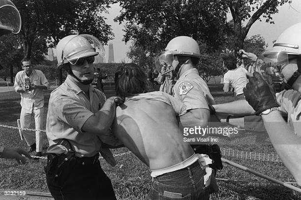 Cigarsmoking police officers arrest a protester at a riot in Grant Park during the Democratic National Convention Chicago Illinois