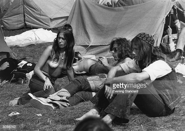 A topless fan soaking up the sunshine with her friends at the Isle of Wight Pop Festival in 1970