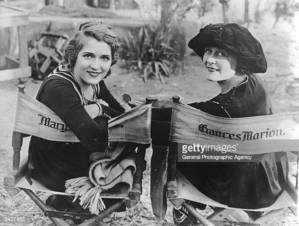 Actress Mary Pickford and director Frances Marion sitting on their personalised canvas chairs on the set of the United Artists war drama 'Straight is...