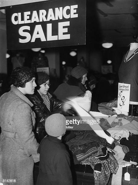 Bargain hunters at the jumper counter in a London westend store