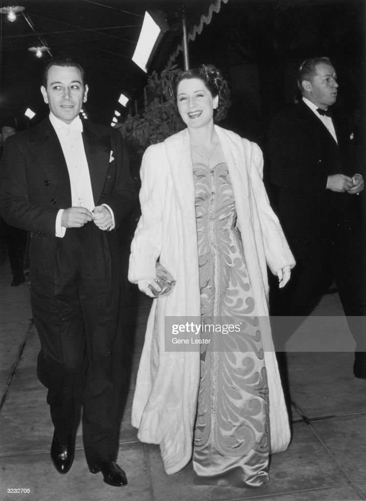 Full-length image of American actor George Raft (1895 - 1980) and Canadian-born actor Norma Shearer (1900 - 1983) attending the Hollywood premiere of director Victor Fleming's film, 'Gone With The Wind,' California. Raft wears tails and a white bow tie; Shearer wears a floor-length gown and matching white fur coat.
