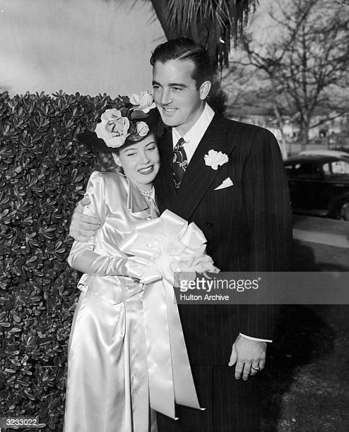 American actor Gloria DeHaven smiles with her new husband actor and singer John Payne as they stand outdoors after their wedding She wears a hat...
