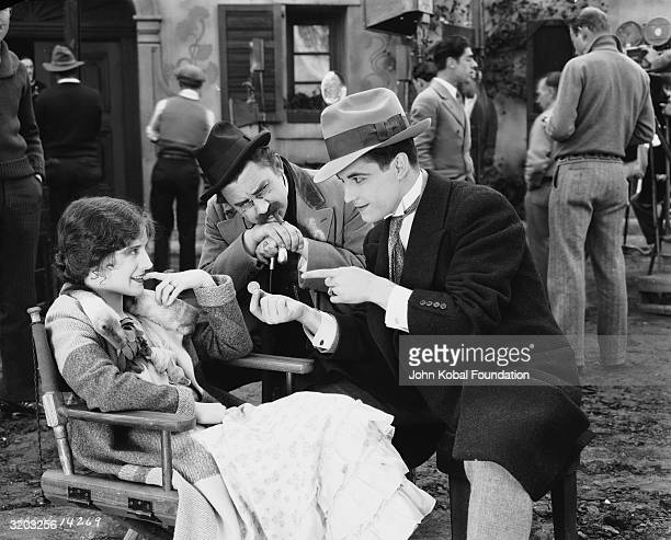 Ramon Novarro performs a magic trick for costars Norma Shearer and Jean Hersholt on the set of 'The Student Prince in Old Heidelberg' directed by...