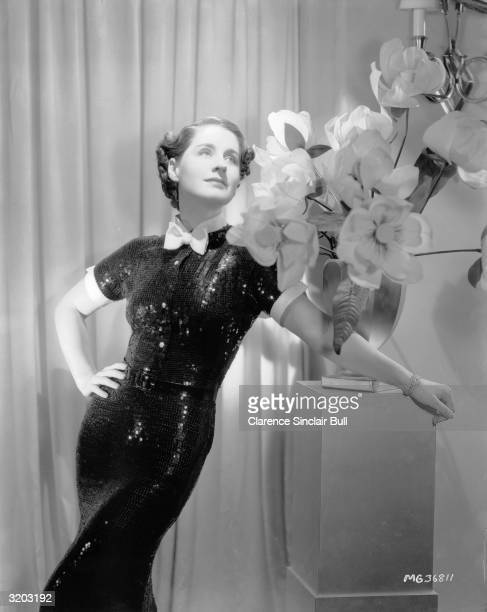 Canadian actress Norma Shearer wearing a shimmering sequinned evening dress with a white bow at the neck