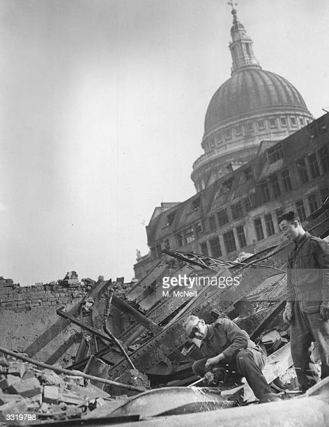 Royal Engineers using welders on girders to clear up bomb damage in front of St Paul's Cathedral in the City of London