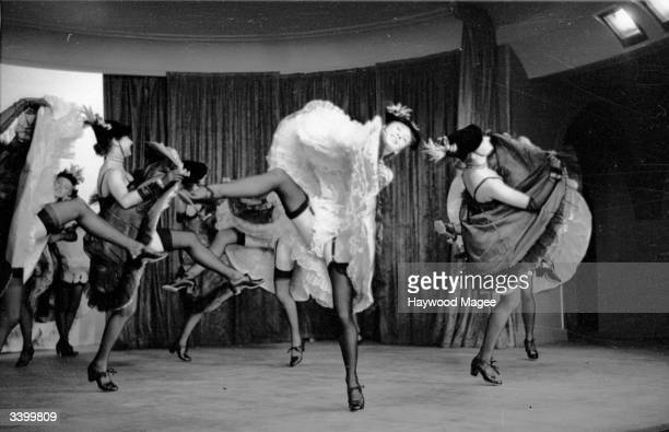 A troupe of cancan dancers leave little to the imagination during a performance of 'The Blue Bird' a cabaret show at London's Pigalle restaurant...