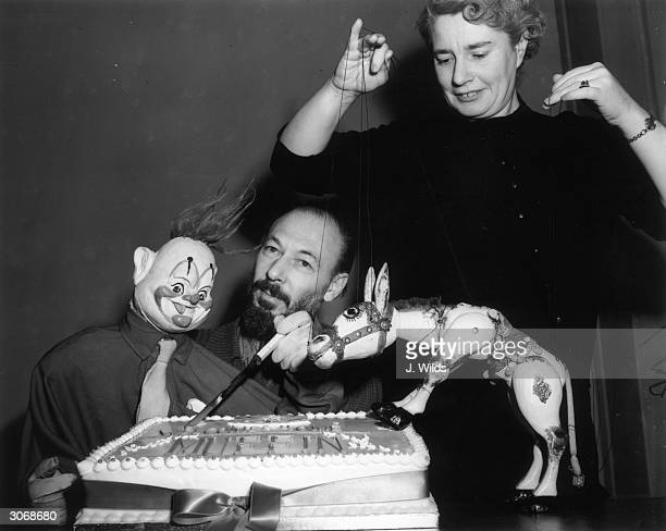 Ann Hogarth and her husband Jan Bussell cocreator and operator of television puppets Muffin the Mule and Rufus the Clown rehearse cutting a...