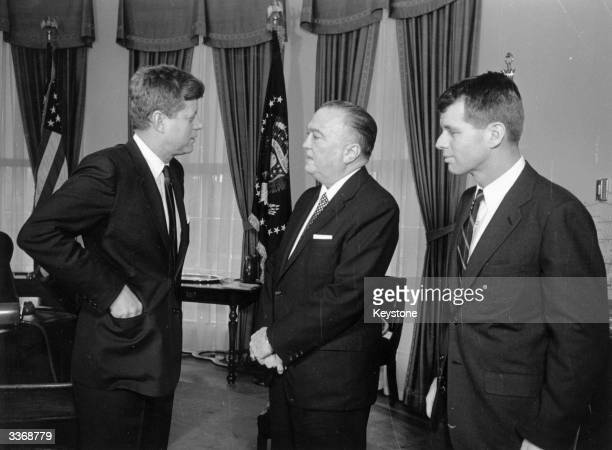 American President John F Kennedy at the White House with his brother Attorney General Robert Kennedy and head of the FBI J Edgar Hoover .