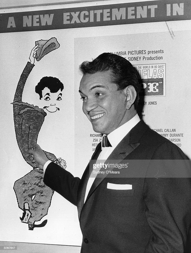 Cantinflas points proudly to a poster of himself at the Columbia film theatre on Shaftestbury Avenue, London, W1.