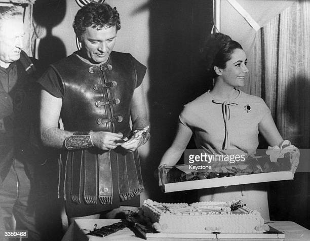At Pinewood studios film star Elizabeth Taylor with a bouquet of roses and a cake presented to her on the occasion of her 31st birthday. Looking on...