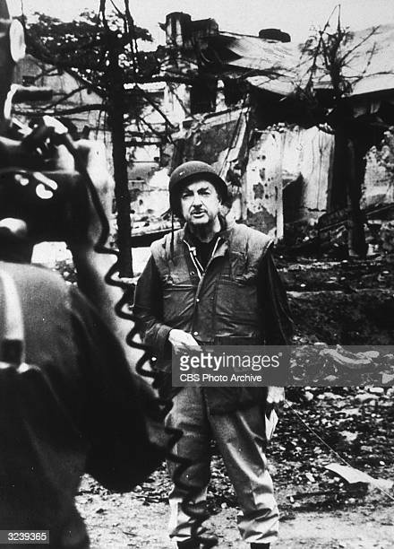 American broadcast journalist Walter Cronkite gives a report in a bombed out area while covering the Vietnam War for CBS News
