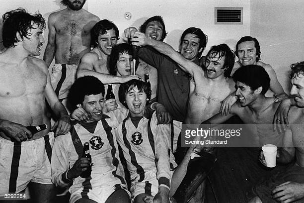 Footballer Peter Kitchen pours a bottle of beer over Glen Roeder as Leyton Orient celebrate their win over Chelsea in the changing room.