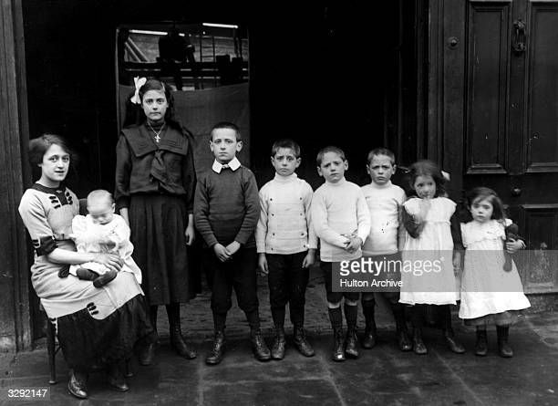 Ada Wayter with her eight brothers and sisters whom she rescued from a fire at their home in Battersea Rise. The children, lined up in identical...