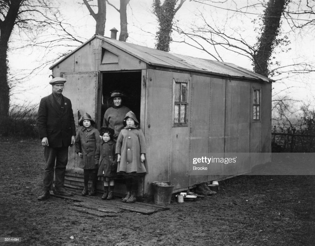 A demobbed soldier with his family standing outside a canvas hut at Ongar, Essex.