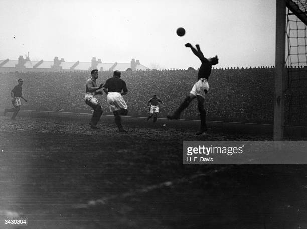In the fourth round of the FA Cup at Highbury Lewis the Arsenal goalkeeper punches the ball away while teammate Parker charges Everton player Dixie...