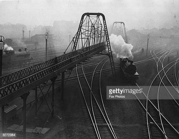 A suspension bridge vaults over the tangle of tracks at Crewe junction