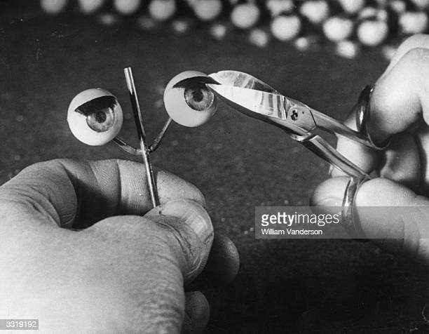 A worker trims the eyelashes on a pair of doll's eyes at a factory in Totton Southampton which specialises in the manufacture of doll parts