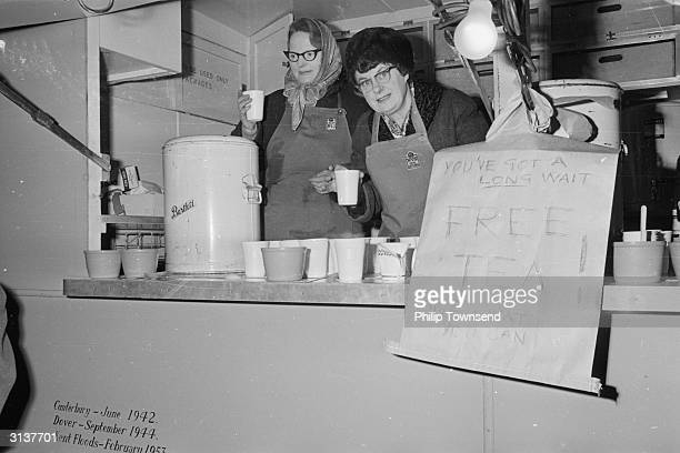 Two members of the Womens Voluntary Service serving free cups of tea to the crowds of people queuing to see Winston Churchill lying in state at...