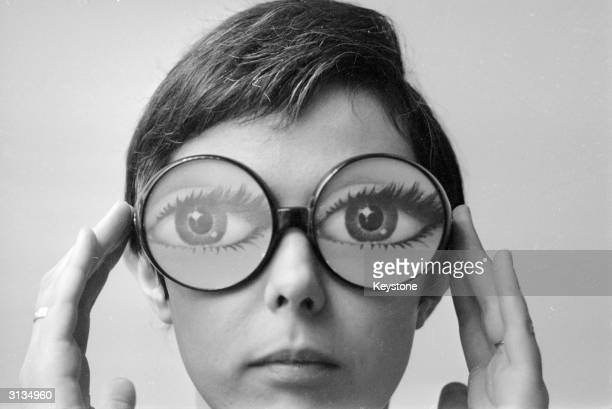 Big round glasses magnify the eyes of the model wearing fashion glasses designed by Marly a Paris optician