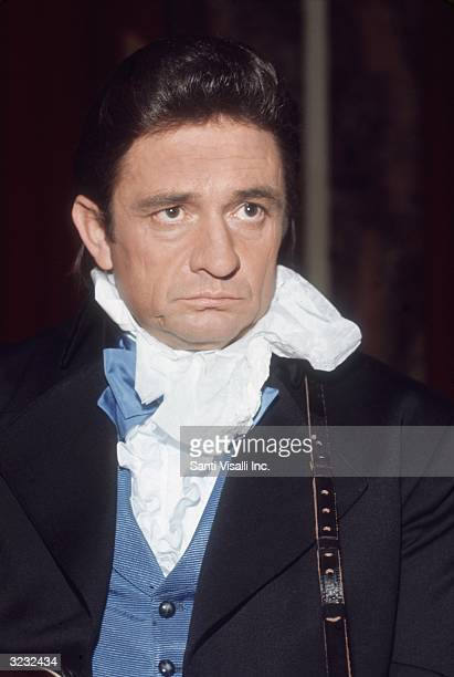 American country singer Johnny Cash , wearing a blue vest and white ascot, prepares for a performance at the Waldorf Astoria Hotel, New York City.