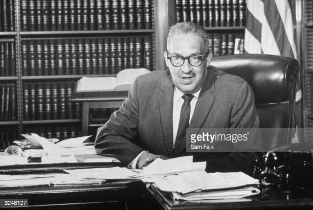 American jurist lawyer associate justice Thurgood Marshall who had been recently appointed Solicitor General by President Lyndon Johnson sits behind...