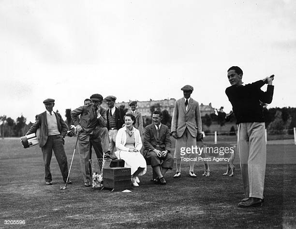 Film actress Norma Shearer watches her husband, producer Irving Thalberg drive off during a game of golf at Gleneagles Hotel, Perthshire.