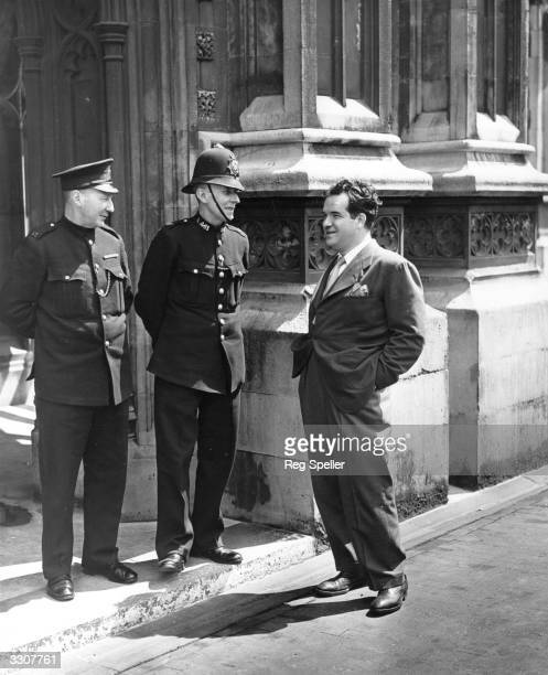 Famous American cartoonist Al Capp, creator of the comic character 'Li'l Abner', talks to two policemen outside the House Of Lords during a visit to...