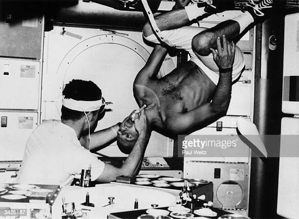 Scientist and Astronaut Joseph P Kerwin performing an oral examinatinon on commander Charles Conrad as he floats weightlessly in Skylab II
