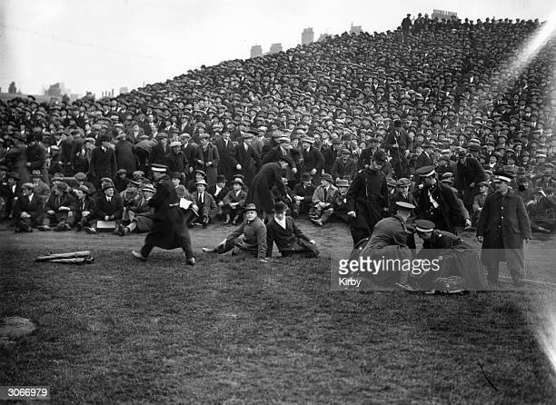 Spectators at a Southampton v Sheffield United football match at Chelsea overflow onto the pitch where one is being attended to by St John's...