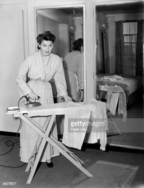 Glamorous film star Ava Gardner takes a break from the glitter to iron her pyjamas