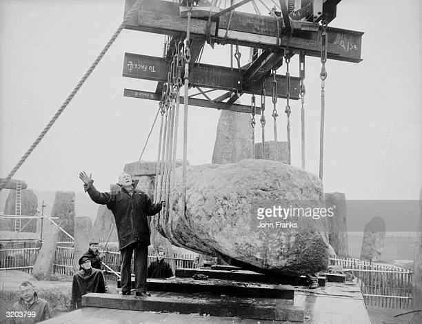 A sixty ton crane one of only two of its kind in the country lifts an eighteen ton lintel of a fallen trilithon at the ancient monument of Stonehenge...